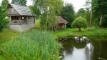 Fotografie idilického Lotyšského venkova, na obrázku v zeleni okolo rybníka stojí několik stavení
