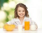 dívka s mlékem a ovocnou šťávou u snídaně k článku s recepty o probiotikach