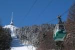 Na obrázku je Liberecká dominanta hotel a vysílač Ještěd, v zasněžené krajině, v popředí je kabinová lanovka vedoucí k vrcholu
