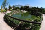 Na obrázku je botanická zahrada v Liberci, v popředí je jezírko, v pozadí se nacházejí skleníky