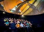 Na obrázku mládež sledující dokument o cestě na měsíc od google, v planetáriu science centra iQLANDIA