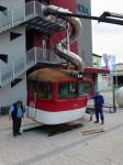 Fotografie stěhování lokomotivy T 478.3 do science centra iQlandia. Na obrázku dělníci pomocí zvedáku vykládají kabinu lokomotivy lidově zvané brejlovec