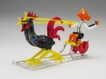 skleněná figurka Hurvínka jedoucího na vozíku taženým kohoutem. Expozice výstavy muzea skla v Jablonci nad Nisou