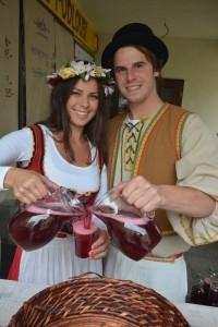 Mladý pár v historických kostýmech rozlévá červený burčák na Znojemském vinobraní