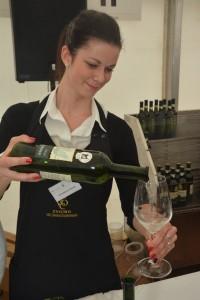 dívka rozlévá víno do sklenice na scéně Znojemského vinobraní