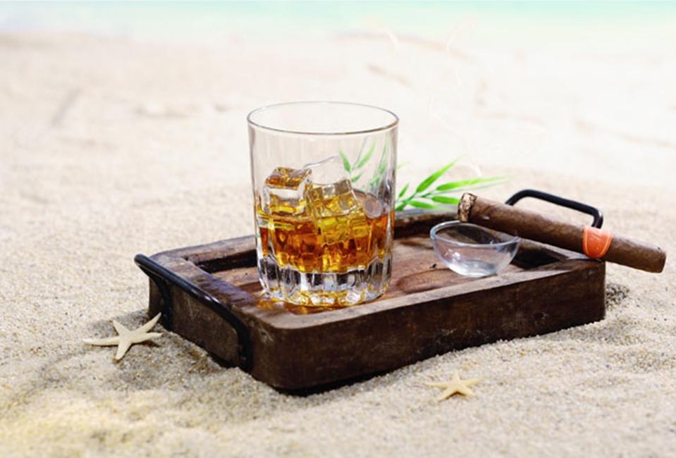 sklenice rumu a doutník na pláži Dominikánské republiky
