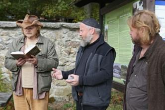 Ćtení z knihy při vylepování qr kódů na turistické cedule v národním parku Šumava